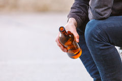 Man depressed with wine bottle sitting on bench outdoor Stock Image