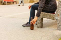 Man depressed with wine bottle sitting on bench outdoor Royalty Free Stock Image