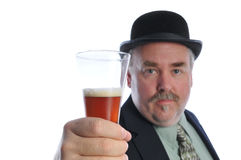 Man in Derby hat holding beer glass. Man with mustache wearing Bowler Derby hat suit and tie holding glass of beer with selective focus on the glass on white Stock Images