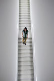 Man descending staircase in white cube gallery Royalty Free Stock Image