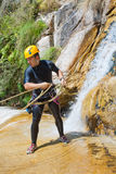 Man Descending Waterfall. Young man descending a waterfall in rappel, praticing canyoning Royalty Free Stock Images
