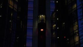 Man Descends in Elevator Outside Building at Night. Man Decends in Elevator Outside Building at Night with reflecting lights and a dotted white halo above his stock video