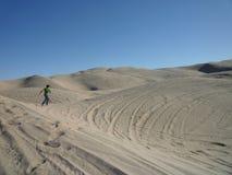 Man in the desert. Man running across dunes in the desert Stock Photos