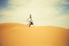 Man in desert. Fashionable man running through the desert Stock Image