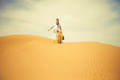 Man in desert. Fashionable man running through the desert Stock Photography