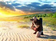 Man in the desert. Man photographs the sunset in the desert stock photography