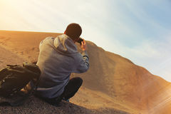 Man in the desert. Takes photo of dune Royalty Free Stock Photos
