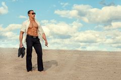 Man in the desert. The man in trousers and a white shirt standing in the desert sand Royalty Free Stock Photos