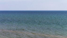 A man on a deserted beach swims on the sea stock footage