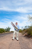 Man on deserted road reading map Stock Photo