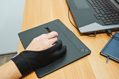 Above view of man hand designer use graphics tablet with touch screen. Man designer freelancer use graphics tablet with touch screen and pen in office stock photo