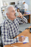 Man at desk drinking from cup Stock Photo
