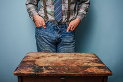 Man at desk with hands in pockets Stock Photo