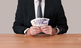 Man at desk holding pounds sterling. It looks like he's playing cards with that money! Deal or no deal royalty free stock photo