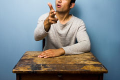 Man at desk making gun gesture Royalty Free Stock Photography