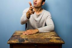 Man at desk making gun gesture Royalty Free Stock Photography