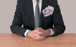 Man at desk with money, UK pounds. Business man in suit with hands clasped and money, UK pounds Stock Photography