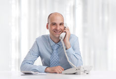 Man at desk in office talking on phone Royalty Free Stock Photos