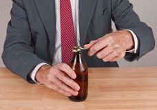 Man at desk opening bottle of cold beer Stock Images