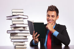 Man at desk reading book Royalty Free Stock Image