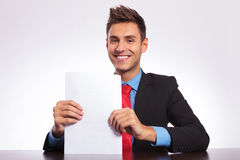 Man at desk showing some papers. Young business man sitting at the desk and holding / presenting a bunch of papers while smiling at the camera stock image