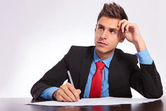 Man at desk thinking what to write. Young business man sitting at the table thinking what to write Royalty Free Stock Photo