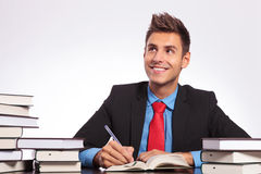 Man at desk thinking & writing. Young business man at a desk full of books, thinking while witing with a smile on his face Royalty Free Stock Photos