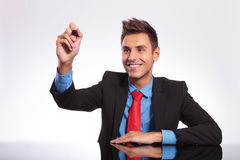 Man at desk writes on imaginary screen stock photo
