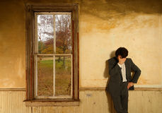 Man in Despair. Man wearing a suit props his head against his hand in despair in an old fashioned abandoned home Stock Photo