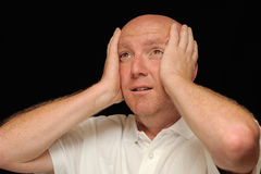 Man in despair. A bald man expressing his despair by holding his head in hands, black background Royalty Free Stock Photo