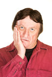 Man in Despair. Despairing mature man with hand on cheek over white Royalty Free Stock Photo