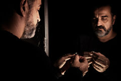 Man in despair sad and lonely looking, looking at a wedding ring in his hands in front of a mirror. In a dark room stock photos