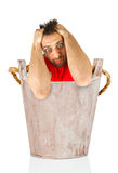 Man with a desperate expression in wooden bucket. Royalty Free Stock Photos