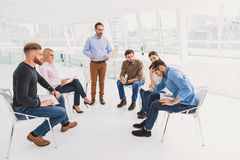 Man in desperation at psychological training. Group of people are sitting and seeing hopeless person with grimace on his face. Serious consultor is standing Royalty Free Stock Images