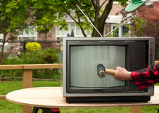 Man destroying old television Royalty Free Stock Images