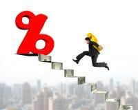 Man det bärande dollarsymbolet in mot procentsatstecken på pengartrappan Fotografering för Bildbyråer