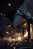 Man det bitande stålröret med många skarpa gnistor på en metallyttersida Royaltyfri Fotografi
