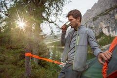 Man det hängande tältet för den avslappnande near sjön som campar dricka den varma drycken Grupp av resan för affärsföretag för v royaltyfria bilder