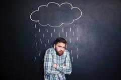Man det känsliga kalla anseendet under regn som dras på svart tavlabakgrund arkivbild