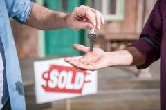 Man det köpande nya huset och tatangenter, sålt tecken bakom royaltyfri bild