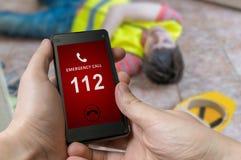 Man det ringande nödläget (nummer 112) på smartphonen sårad arbetare Arkivbild