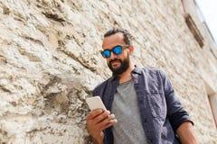 Man det smsande meddelandet på smartphonen på stenväggen Royaltyfria Foton