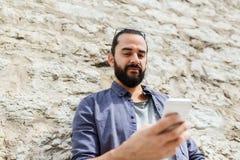 Man det smsande meddelandet på smartphonen på stenväggen Arkivfoto