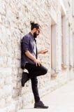 Man det smsande meddelandet på smartphonen på stenväggen Fotografering för Bildbyråer