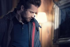 Man detail wearing anorak jacket portrait indoor at home looking down. Europe Alps. Winter evening.  royalty free stock photos