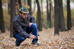 Man detective with a beard exploring footprint on the autumn lea Royalty Free Stock Photography