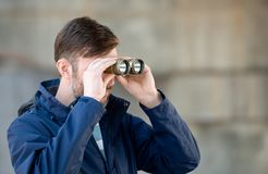 Man detective watches binoculars on a city street. In the daytime stock images
