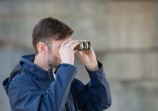 Man detective watches binoculars on a city street. In the daytime stock photos