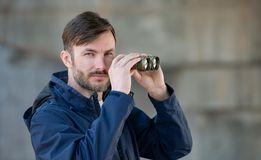 Man detective watches binoculars on a city street. In the daytime royalty free stock images
