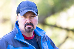 Man with a Determined Attitude. Man with a goatee looking determined attitude on a green sunny background Royalty Free Stock Photo